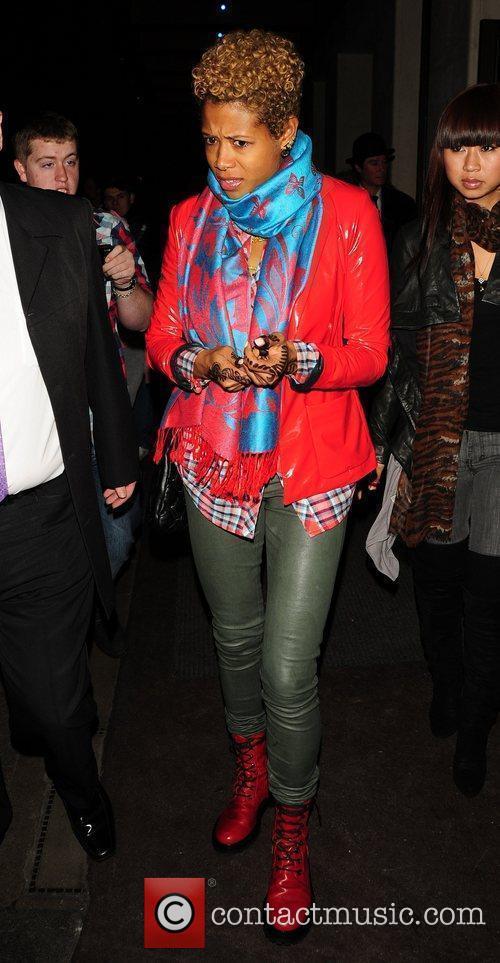 Singer Kellis outside her hotel wearing a red...
