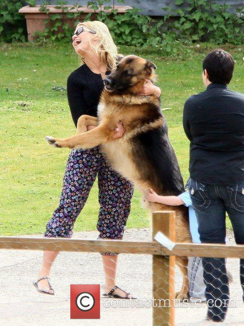 Kerry Katona playing with German Shepherd dog near...