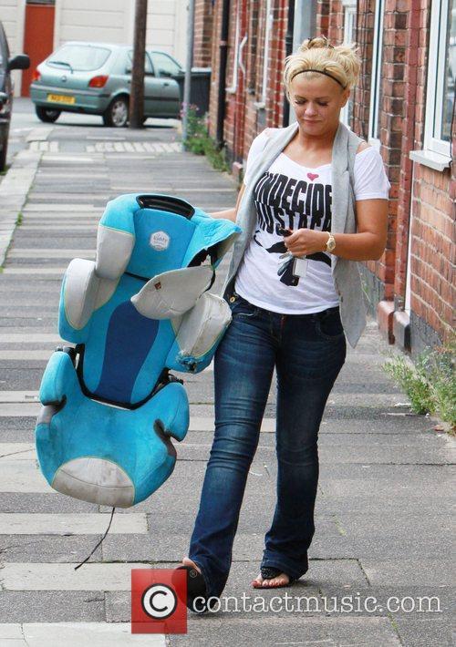 Kerry Katona carrying a child car seat as...