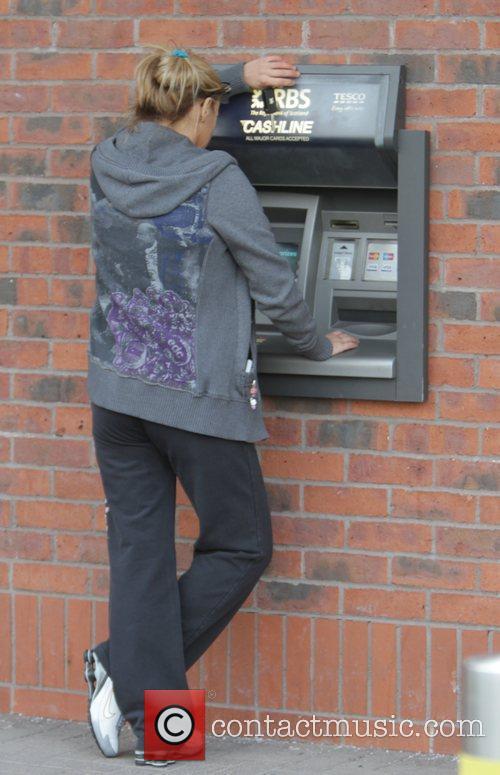 Kerry Katona  using a cash-point machine, while...