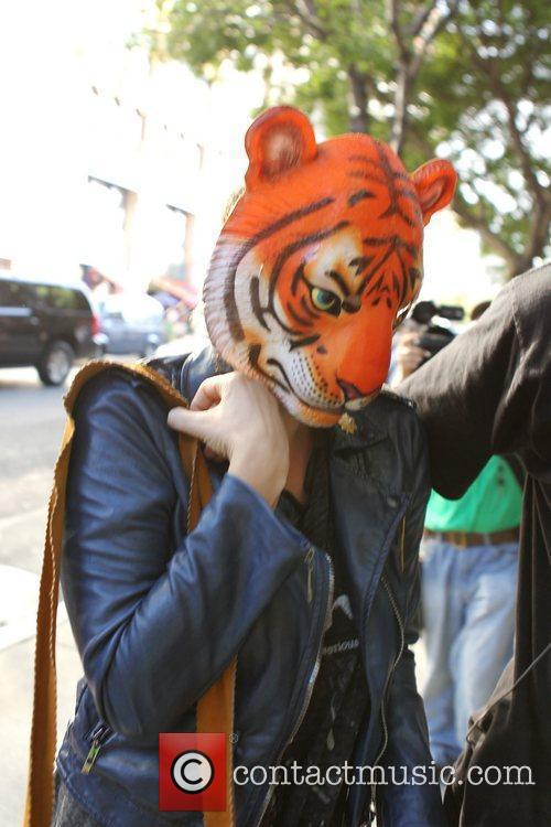 Is seen wearing a tiger mask as she...