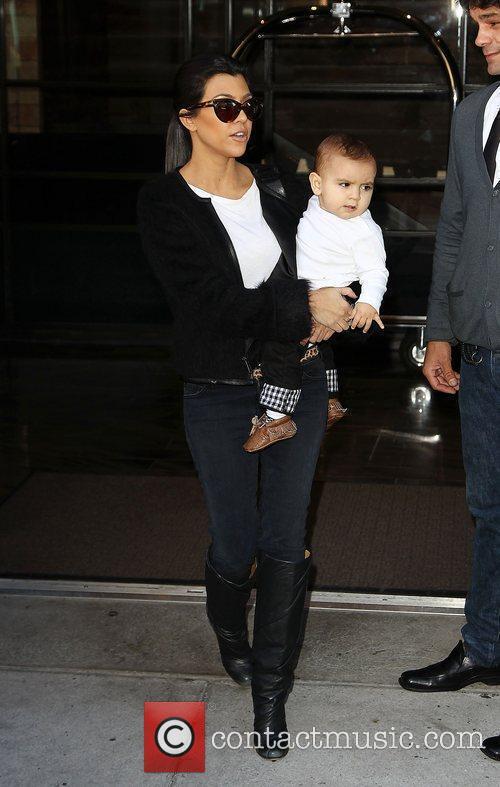 Kourtney Kardashian carrying her son Mason as she...