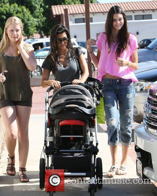 Kourtney Kardashian, Kendall Jenner (R) and a family...