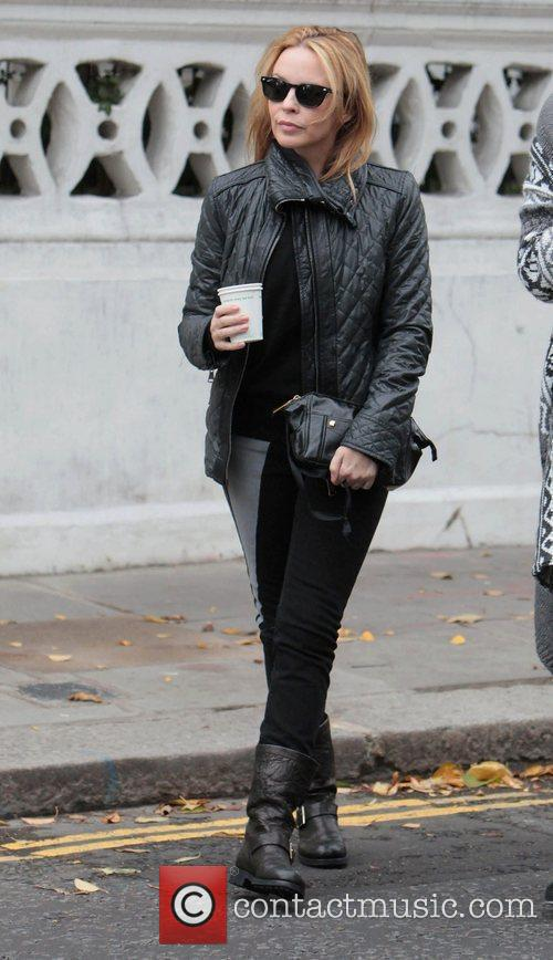 Kylie Minogue sporting a black leather jacket, boots...