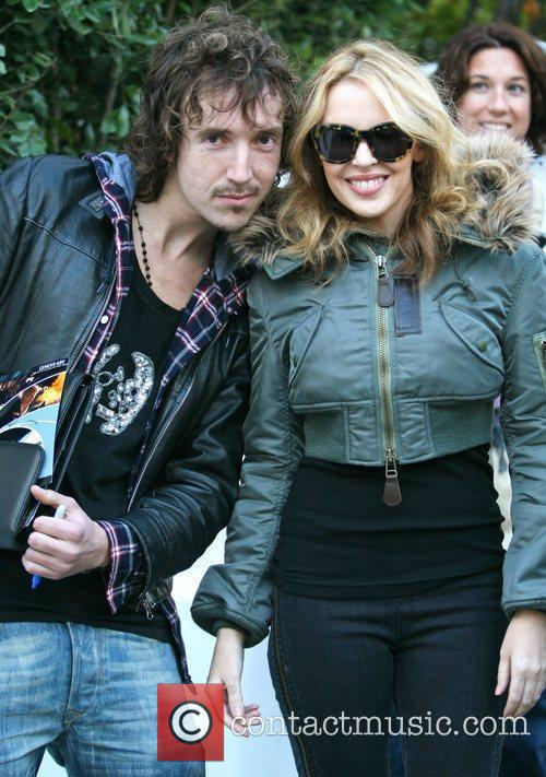 Kylie Minogue poses with a fan leaving her...
