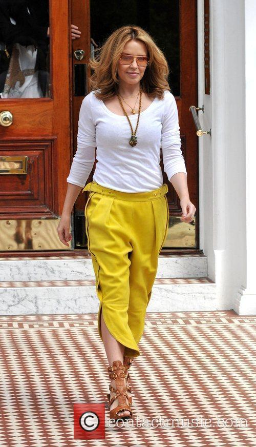 Leaving her home wearing mustard coloured trousers