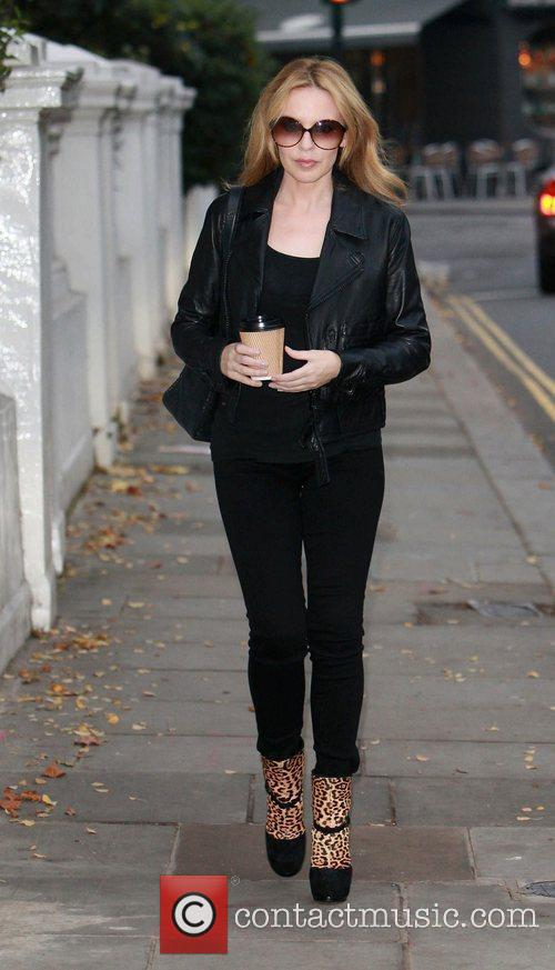 Kylie Minogue leaving her home, carrying a cup...