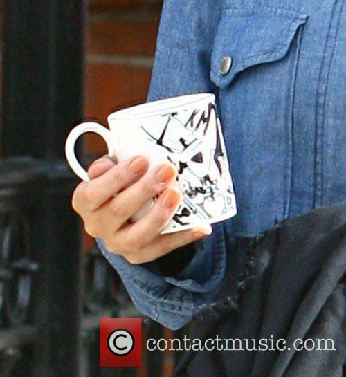 Leaving home, carrying a mug featuring her initials