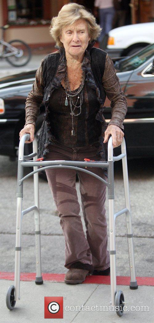 Enters a Medical building with her walker and...