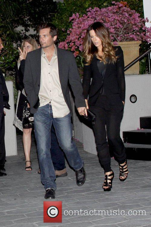 Len Wiseman and Kate Beckinsale holding hands while...
