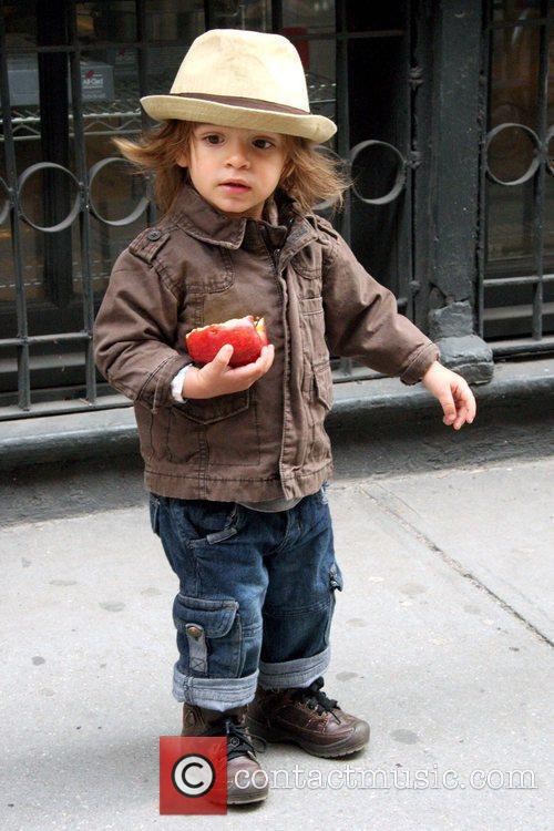 Levi McConaughey eating an apple while walking in...