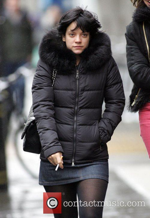 Smokes a cigarette while walking with friends