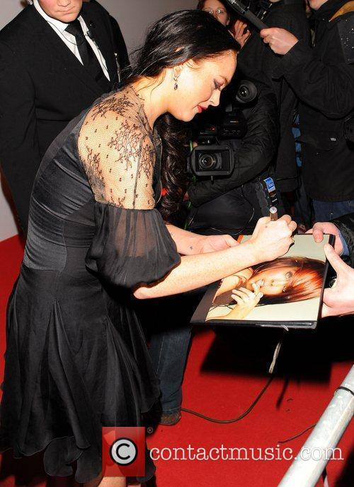 Lindsey Lohan signs autographs as she arrives for...