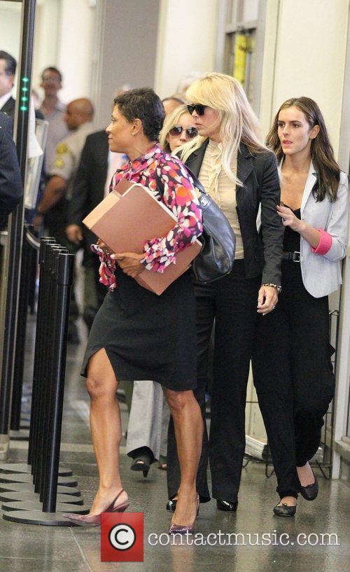 Dina Lohan passes through the metal detector at...
