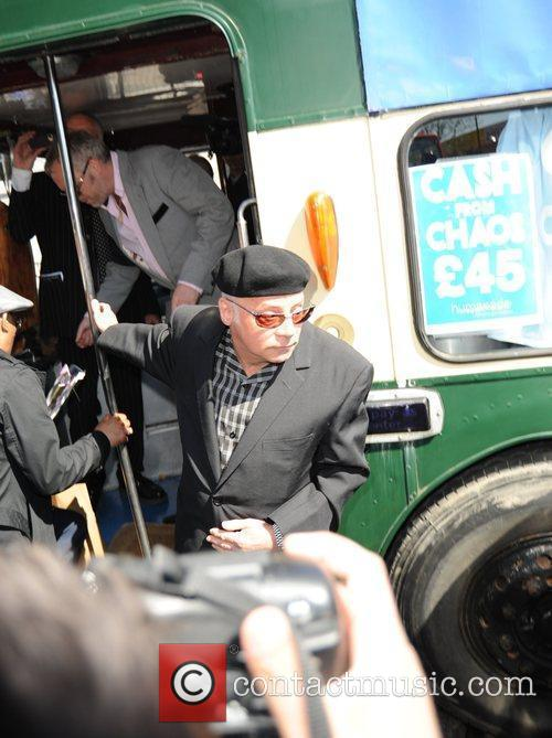 Mourners arrive on a green double decker bus...