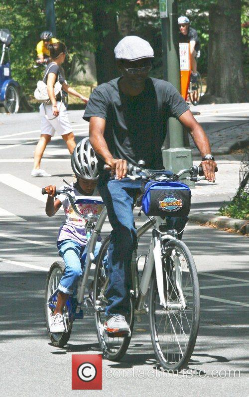 Chris Rock riding a tandem bicycle with his...