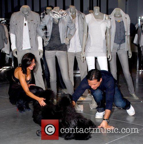 Courtney Mazza and Mario Lopez petting a dog...
