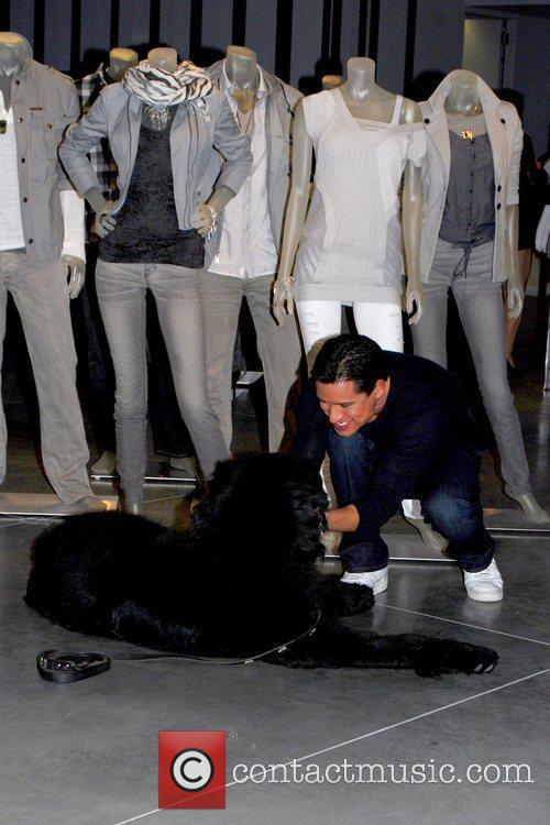 Mario Lopez petting a dog inside Armani Exchange...