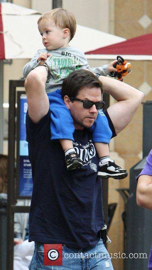 Mark Wahlberg carries his son Brendan on his...