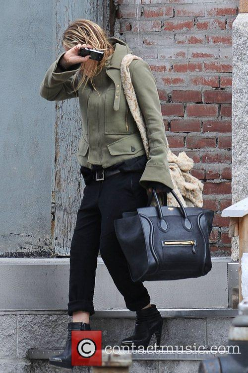 Mary-Kate Olsen covers her face from photographers as...