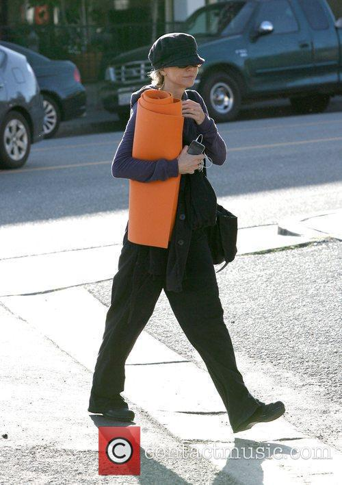 Carrying her orange yoga mat on her way...