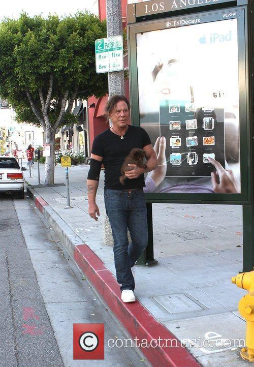 Mickey Rourke and his dog walking back to...