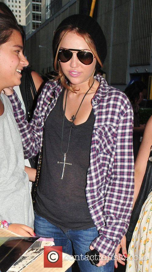 Miley Cyrus wearing a checked shirt and cross...