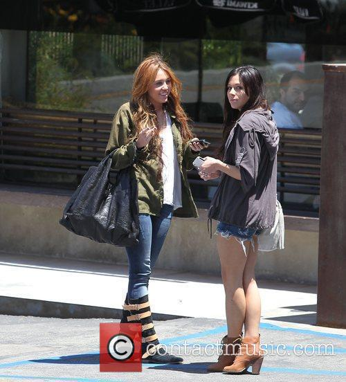 Miley Cyrus and Mandy Jiroux stand talking outside...
