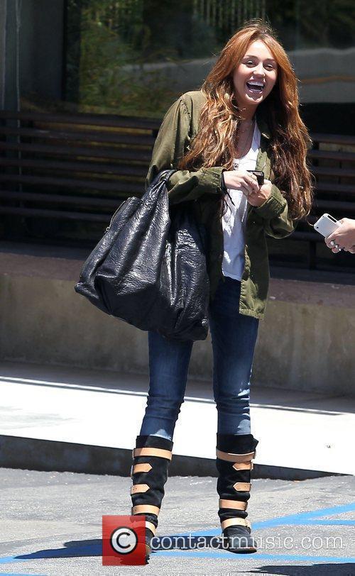 Miley Cyrus stands outside Katsuya restaurant in Studio...
