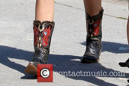Miley Cyrus' cowboy boots Miley Cyrus walking with...