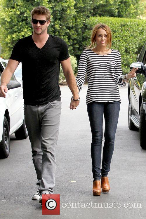 Liam Hemsworth and Miley Cyrus Miley Cyrus holding...