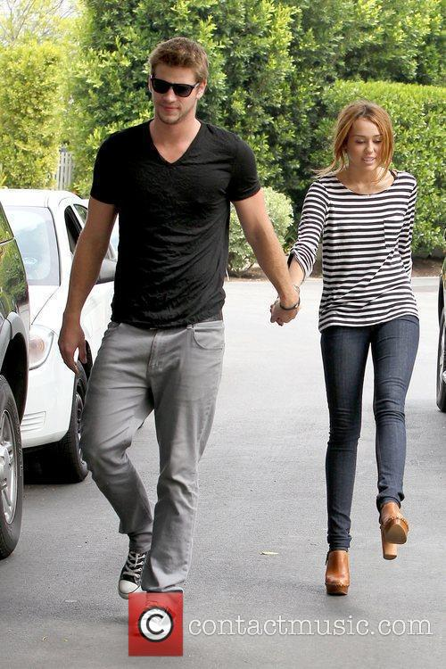 Miley Cyrus holding hands with her boyfriend in...