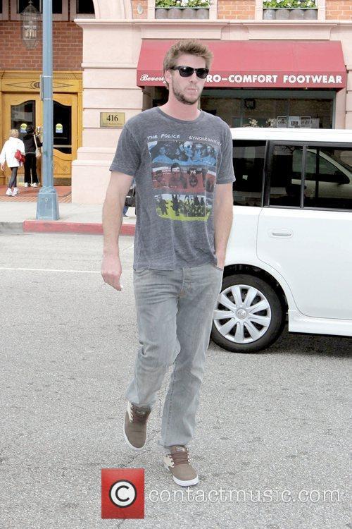 Liam Hemsworth sucking on a lollipop while walking...