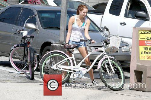 Miley Cyrus rides her bicycle with her boyfriend...