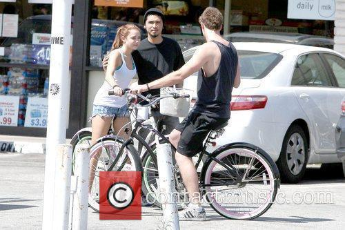 Miley Cyrus with a fan and Liam Hemsworth...