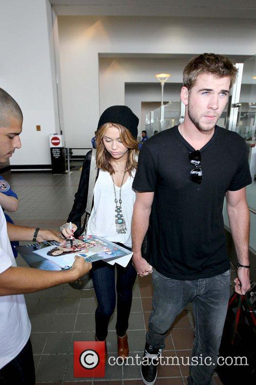 Miley Cyrus signing an autograph and Liam Hemsworth...