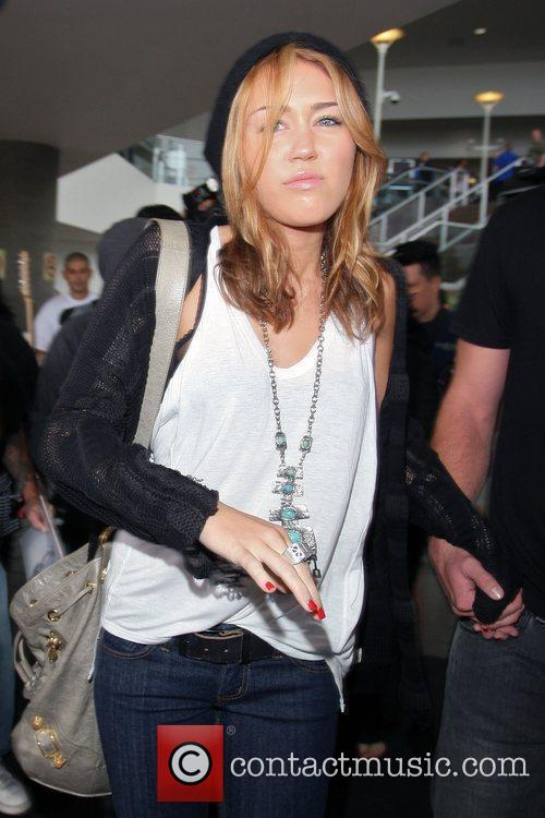 Miley Cyrus, looking exhausted, arrives at LAX airport...