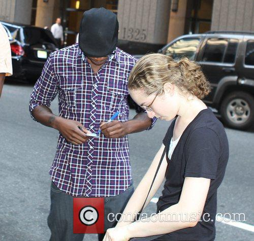 Ne-Yo signs autographs for fans outside his hotel...