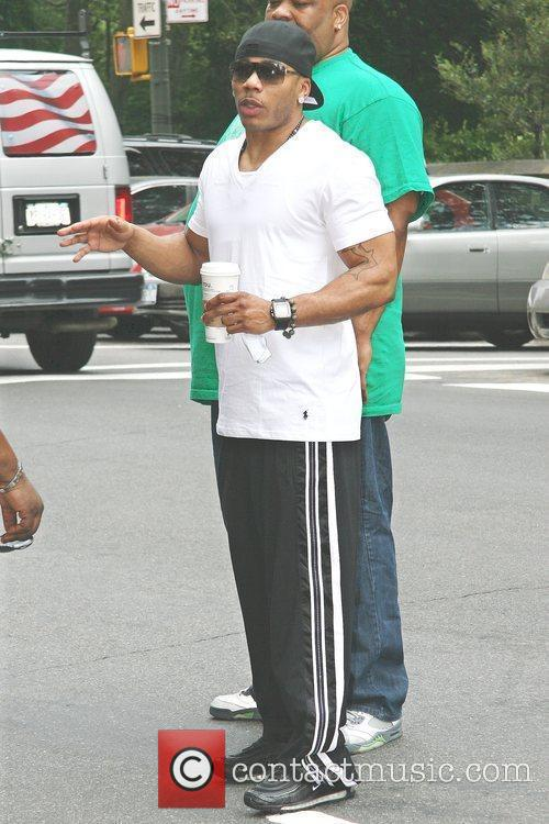 Nelly leaving his Manhattan hotel carrying a large...