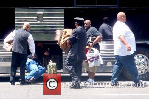Removing luggage from his tour bus outside his...
