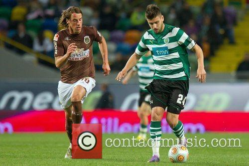 Miguel Veloso from Sporting vies the ball with...
