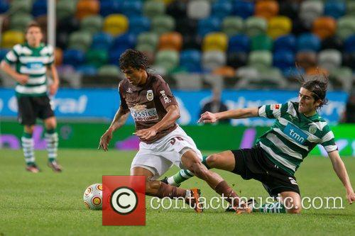 Pedro Mendes from Sporting vies the ball with...