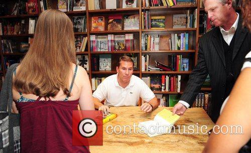 Signs copies of his new book 'Safe Haven',...