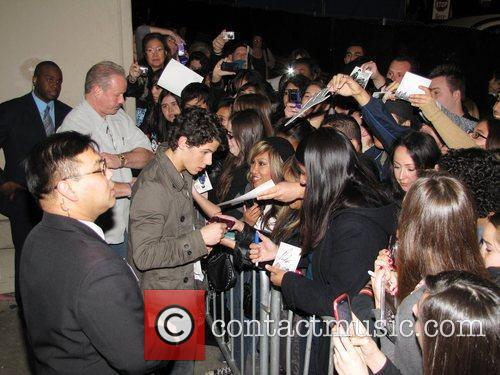Nick Jonas of the Jonas Brothers signs autographs...