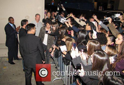 Signs autographs for fans outside a studio