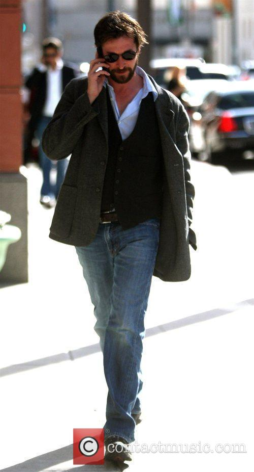 Noah Wyle talks on his mobile phone while...