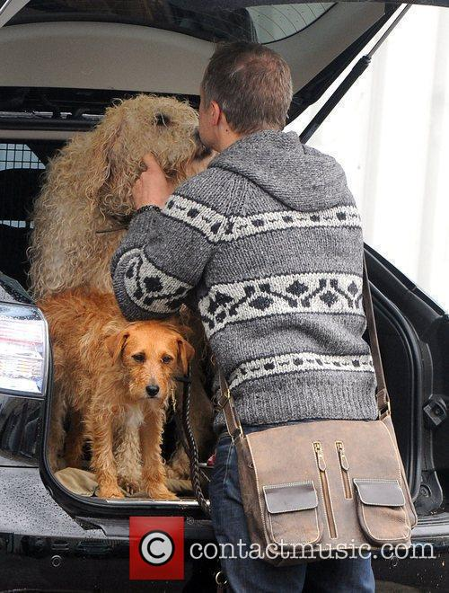 Kisses his dog as he arrives at the...