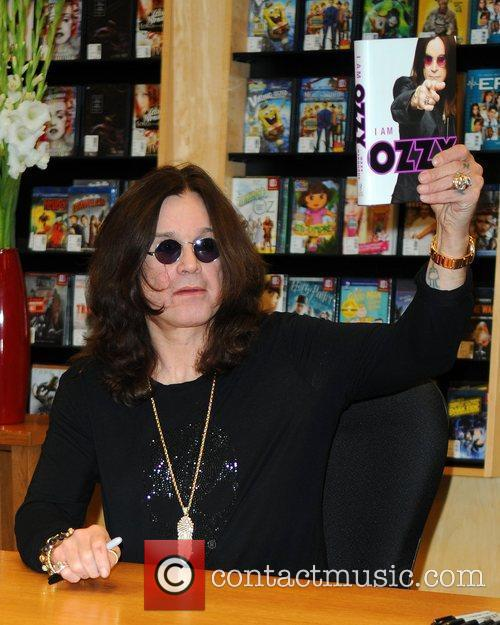 Signs copies of his book 'I Am Ozzy'...