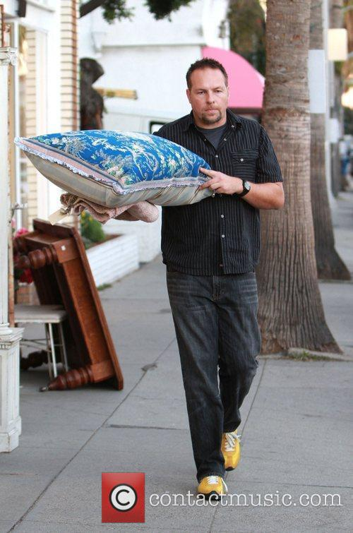 A shopkeeper carries one of Pamela Anderson's pillows...
