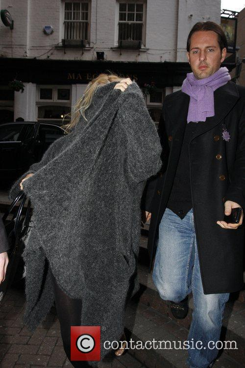 Pamela Anderson covering her face as she leaves...